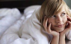 Chica tumbada en la cama pensativa en comprar un colchon