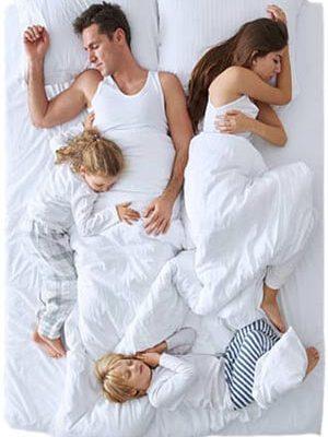 Familia de cuatro mienbros durmiendo todos juntos en una cama