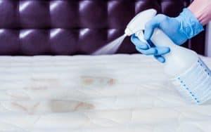 Una mujer limpiando manchas del colchón con pulverizador humedeciendo la zona