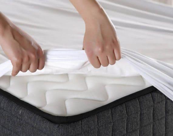 persona colocando un protector de colchón para su protección y evitar que se ensucie
